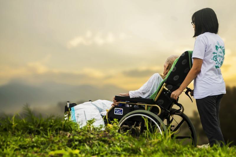 Idős családtag a szabadban gondozójával